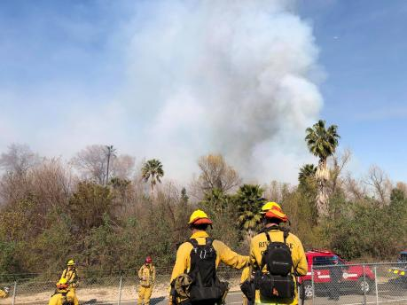 Firefighters in the foreground while smoke from riverbottom fire is in background
